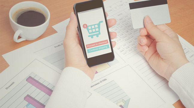 ecommerce marketing featured image - person holding a credit card and a smartphone with a shopping cart icon on display