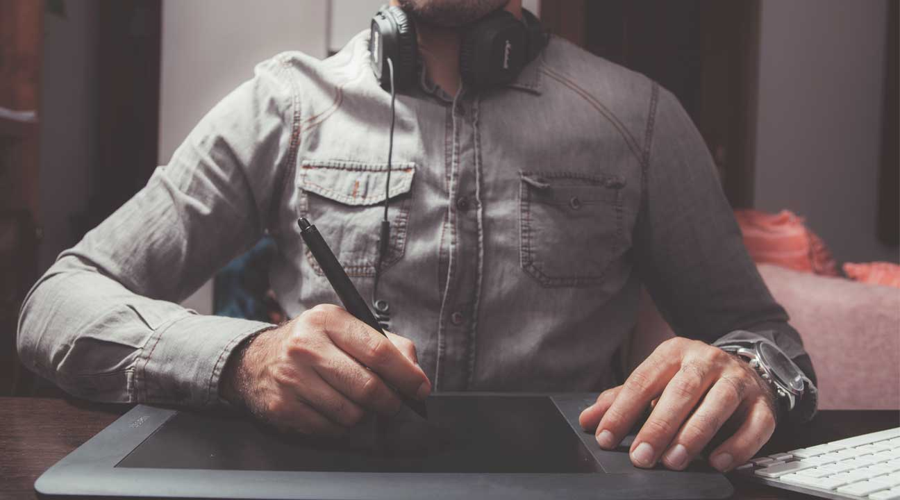 Know Your Worth As A Designer - designer working with a graphic pen and tablet with headphones
