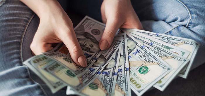 woman holding us dollar bank notes